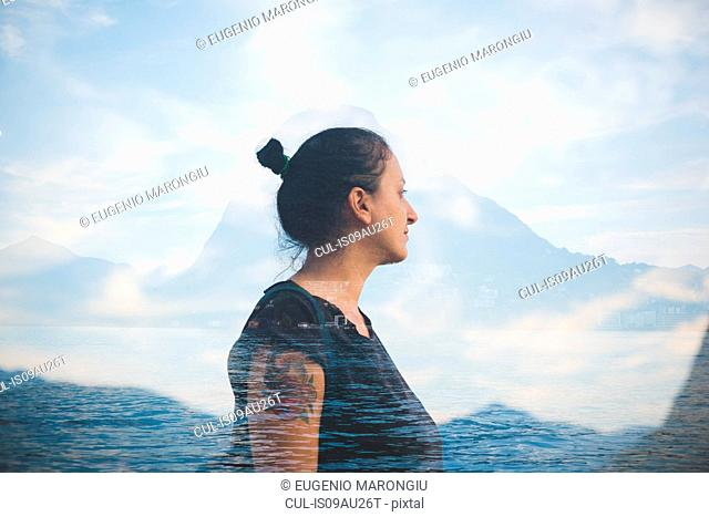 Double exposure of mid adult woman looking out at Lake Lugano, Switzerland