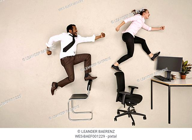Business colleagues walking on chairs towards office desk