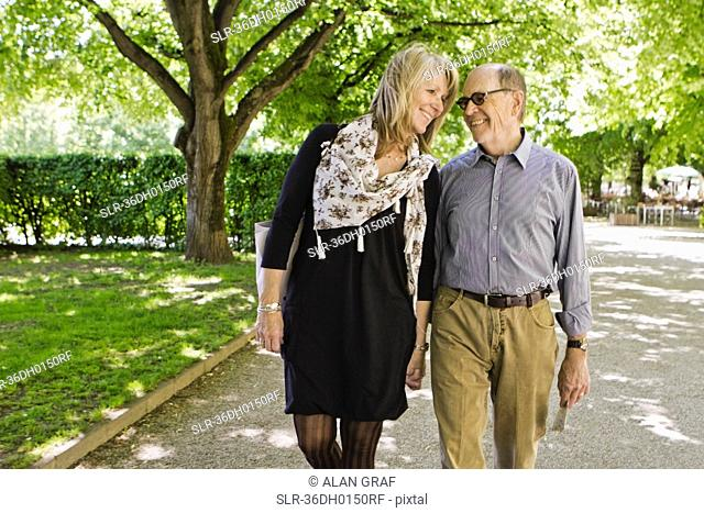 Older couple walking hand-in-hand