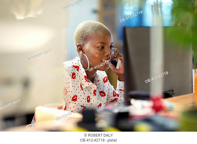 Businesswoman talking on smart phone, working at computer in office