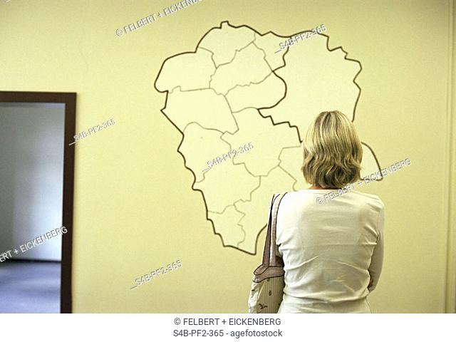 Woman standing in front of the sketch of a map on a wall