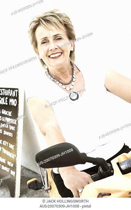 Portrait of a mature woman sitting on a motor scooter and smiling