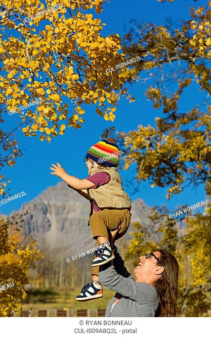 Mother holding up toddler amongst autumn trees