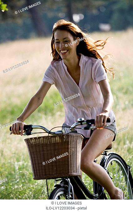 A young woman riding a bicycle in summertime