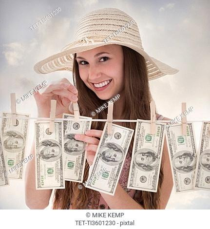 Woman hanging 100 dollar bills on clothesline