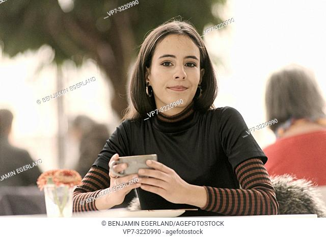 portrait of content woman holding coffee cup while sitting at table in café, in Munich, Germany