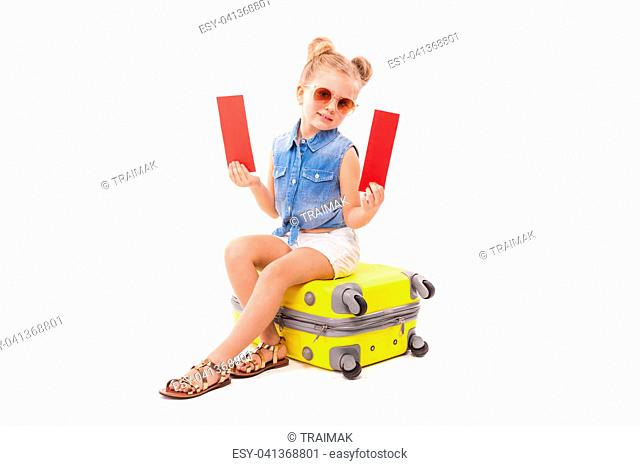 Isolated on white, pretty little caucasian blonde girl in blue jeans shirt, white shorts, sunglasses and sandals sit on the yellow suitcase