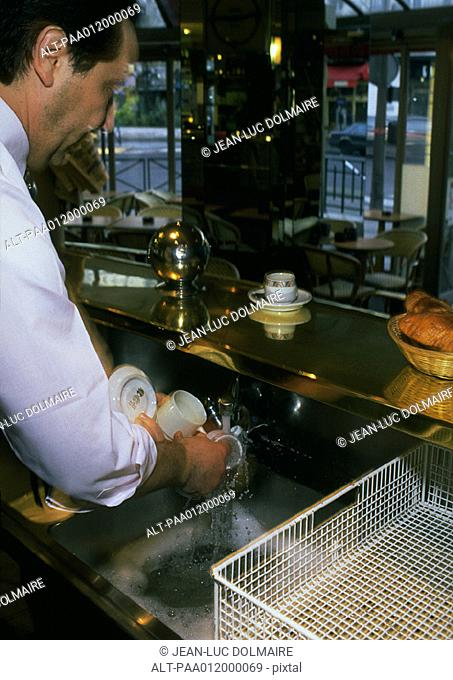 Man washing glasses in cafe