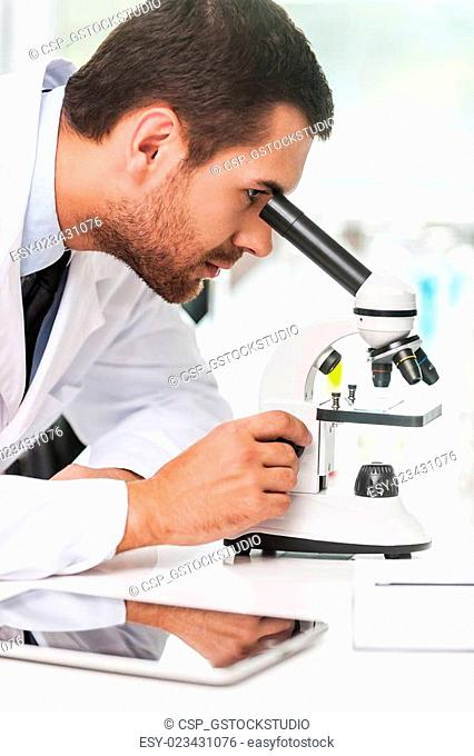 Research and development. Side view of concentrated young scientist in white uniform using microscope while sitting at his working place