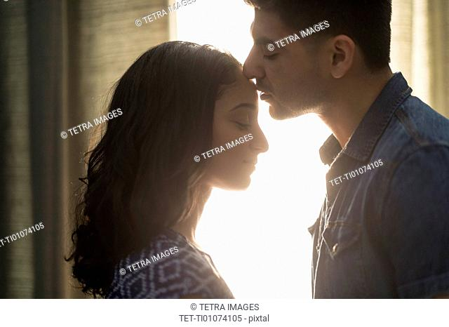Young couple kissing in sunlight