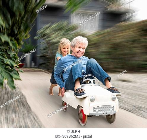 Grandson pushing grandmother on his toy car