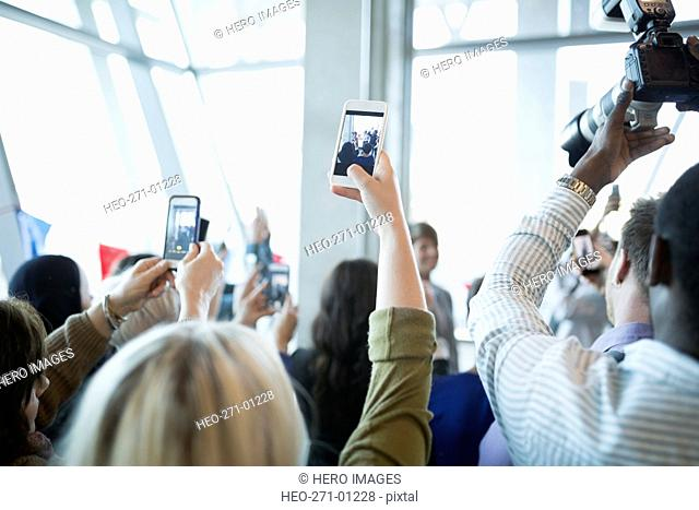 People photographing political rally with camera phones overhead