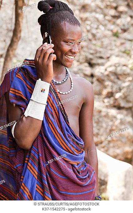 Maasai man wearing traditional dress and using modern smart phone
