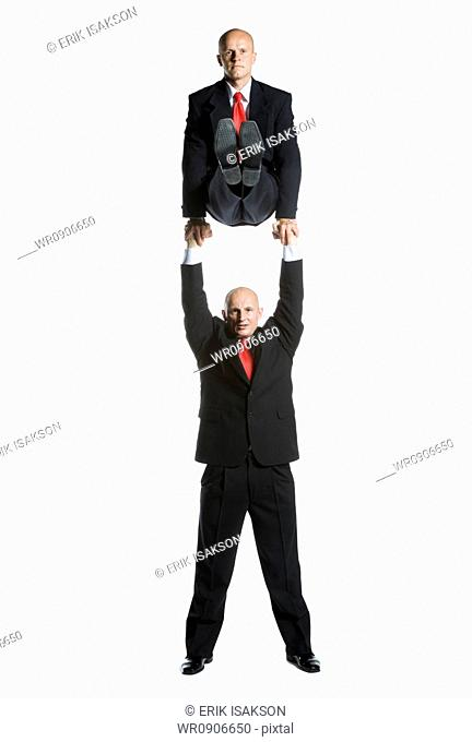 Portrait of two male acrobats in business suits performing