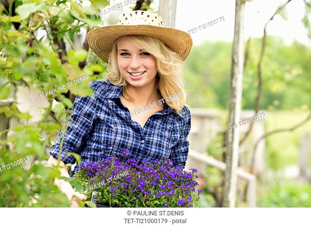 Portrait of young woman holding potted flowers