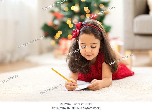 little girl writing christmas wish list at home