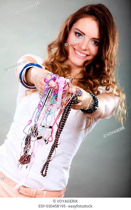 Happy pretty young woman wearing bracelets and rings holding many plentiful of precious jewelry necklaces beads. Portrait of gorgeous fashion girl in studio on...