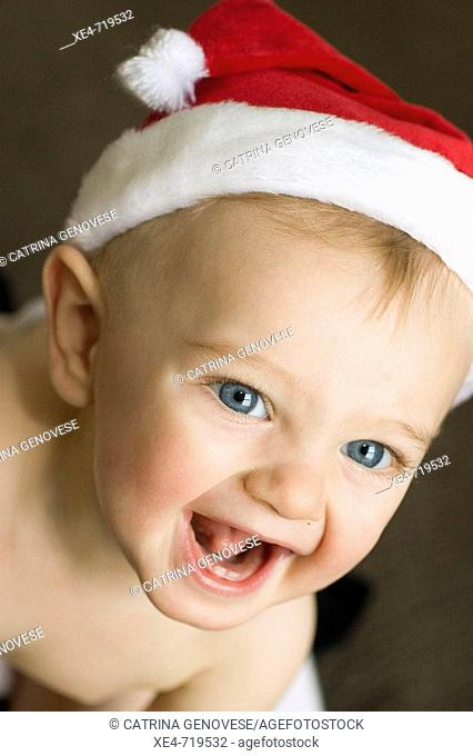 9-10 month old baby boy in Santa Claus hat at Christmas