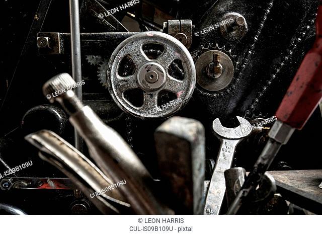Tools near printing machinery in printing press workshop