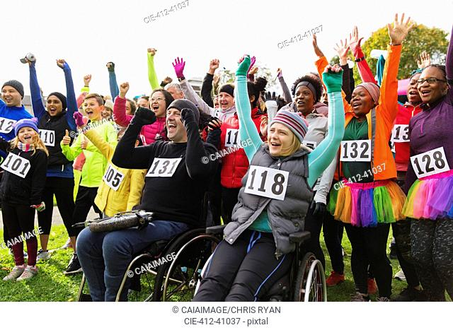 Enthusiastic crowd cheering at charity race in park
