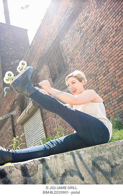 Caucasian woman tying roller skate near brick wall