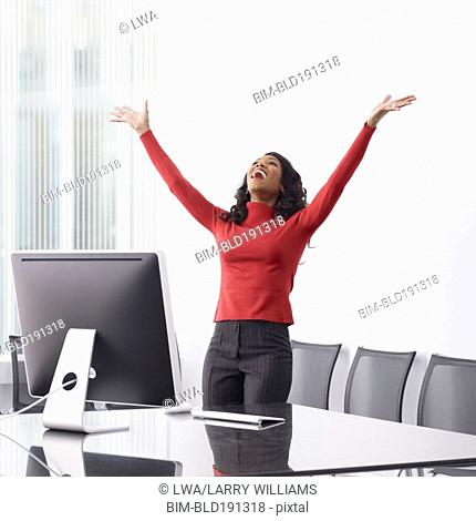African businesswoman celebrating in office