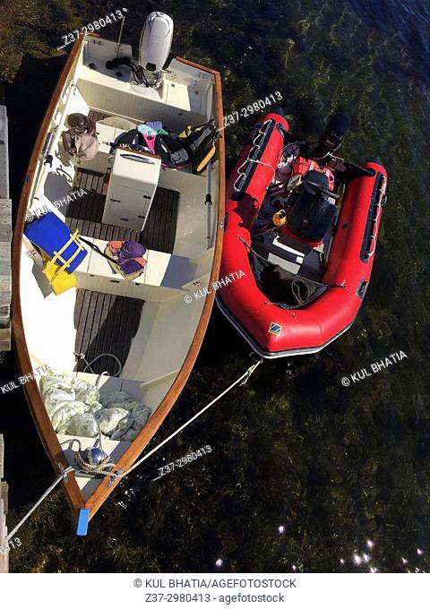 Looking down on a wooden boat and a rubber dinghie tethered to a dock, Nova Scotia, Canada