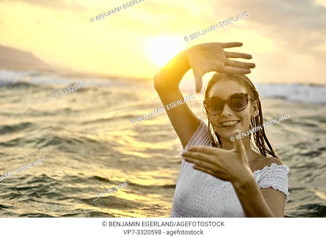 young woman framing hands around face, at beach during sunset, in Crete, Greece