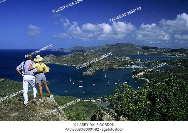 The Caribbean, Antigua, Shirley Heights lookout, Couple overlooking scenic bay and harbor