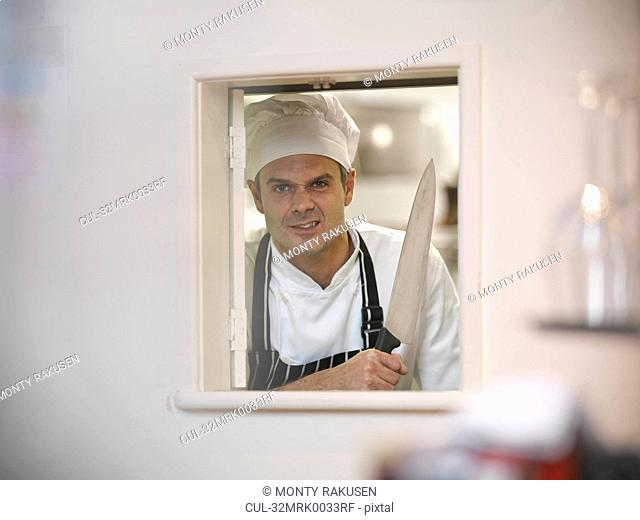 Chef holding large knife in restaurant