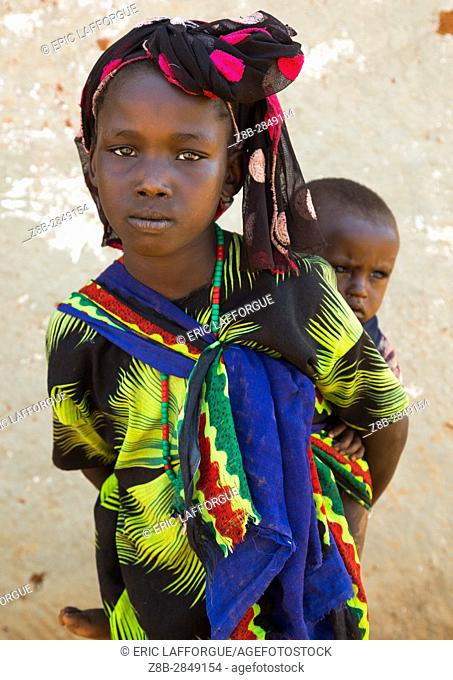 Portrait of a Borana tribe girl carrying her brother on her back, Oromia, Yabelo, Ethiopia