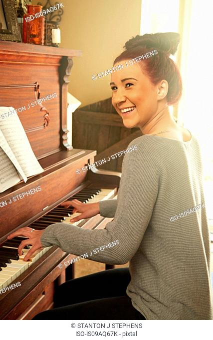 Young woman playing piano in living room
