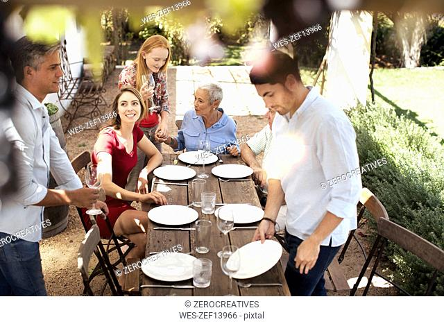 Family setting table outside for lunch