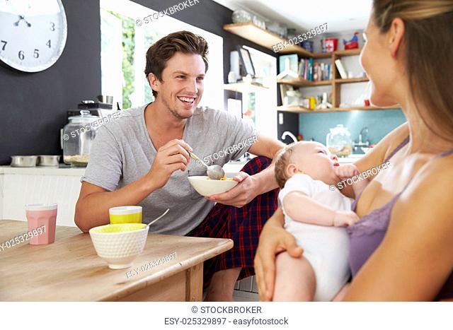 Family With Newborn Baby Daughter At Breakfast Table