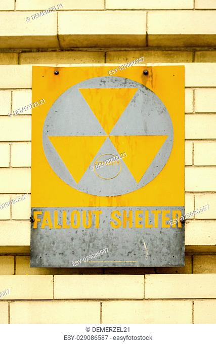 Atomic nuclear fallout shelter sign with radiation symbol on a brick wall