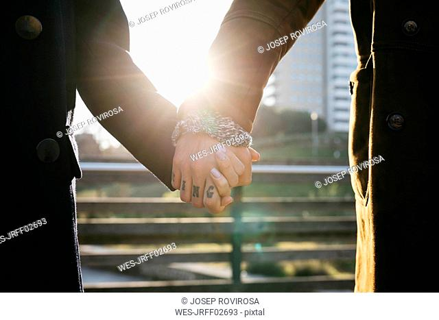 Close-up of couple holding hands in backlight