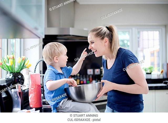 Mother and son fooling around whilst baking, son putting mixture on mother's nose