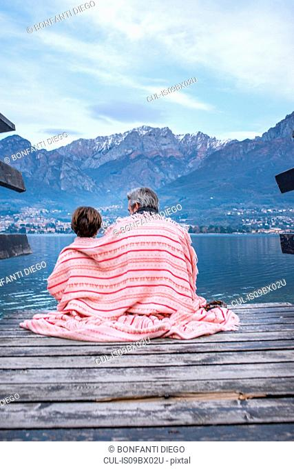 Boy and father wrapped in blanket on lakeside pier, rear view, Lake Como, Onno, Lombardy, Italy