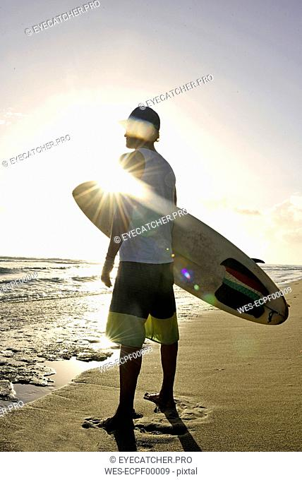Man with surfboard standing on the beach watching sunset