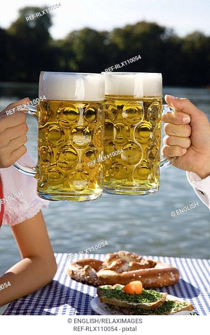 Close-up of young couple drinking beer in Seehaus, beer garden, Munich, Germany