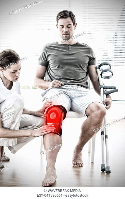 Composite image of physiotherapist examining man with crutches