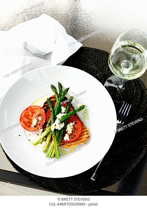 Plate of fish, asparagus and tomato