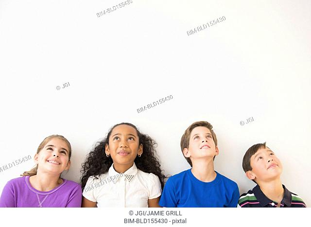Smiling children thinking and looking up