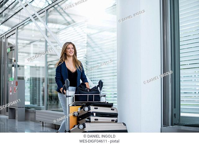 Smiling young woman pushing luggage trolley