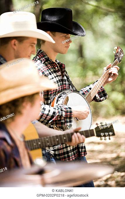 Portrait of young cowboys playing musical instruments outdoors