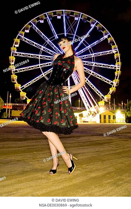 A beautiful pin up model posing infront of a ferriswheel at night