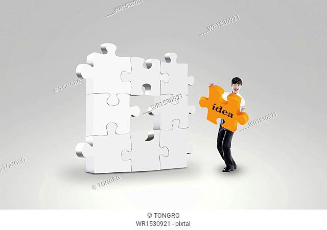 a business man holding a puzzle piece
