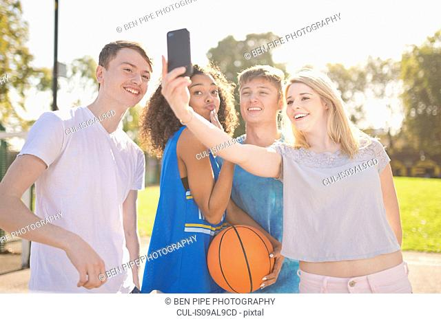 Four young adult basketball players taking smartphone selfie