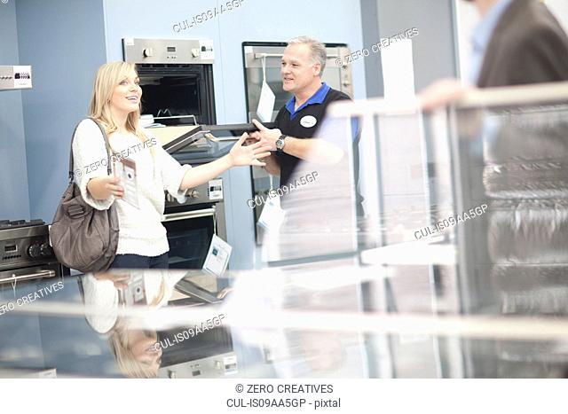 Young woman and salesman looking at ovens in showroom