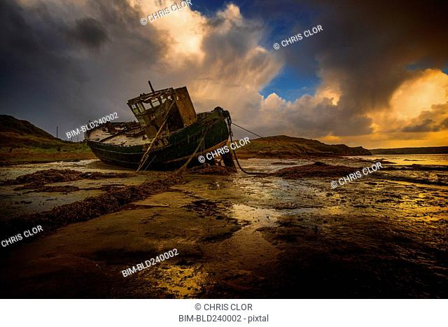 Shipwreck on beach at sunset